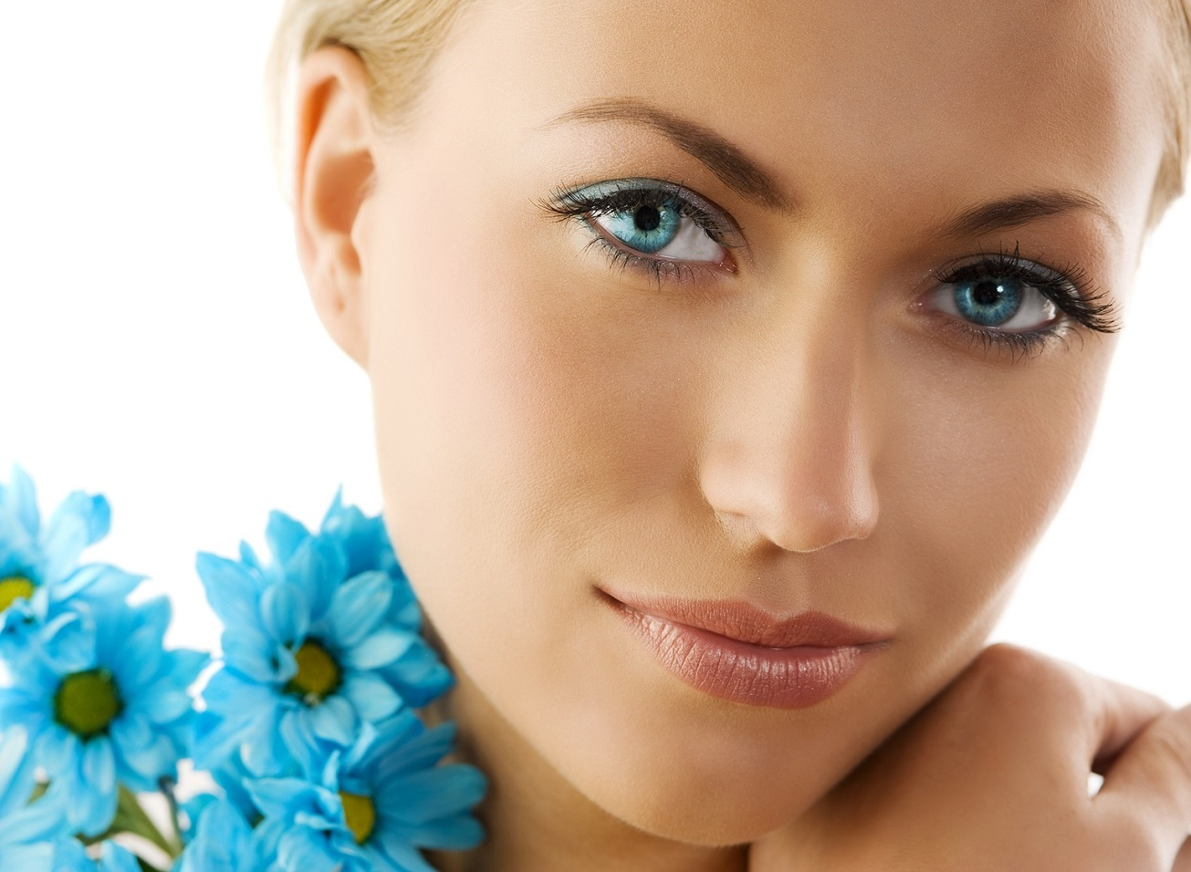 close up of a cute woman with big eyes and blue daisy